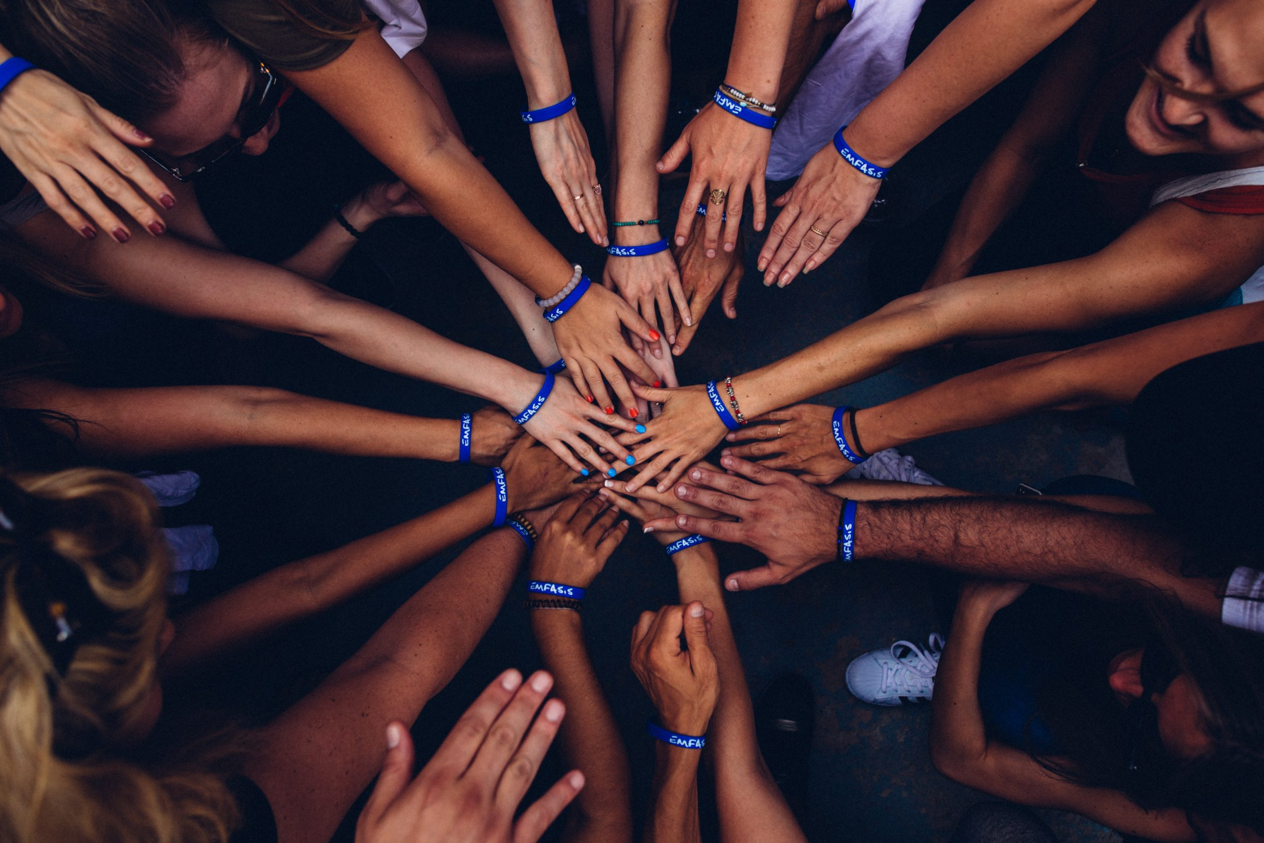 image of group of people putting their hands together in support